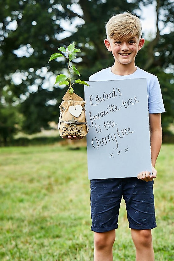Edward holding a baby roots wild cherry tree gift