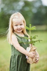 young girl holding a baby roots christmas tree