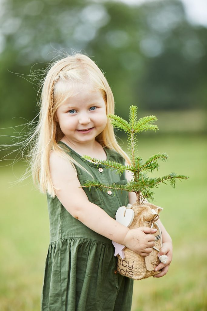 Girl holding Baby Roots Christmas Tree Gift
